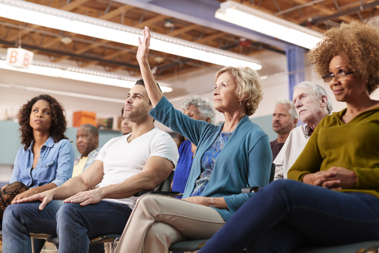 Older woman raises hand to ask a question at a community presentation