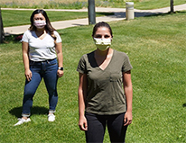 two students standing on grass, masked