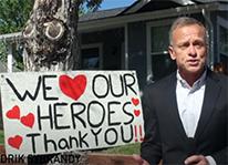 newscaster standing next to heros/heart handmade sign