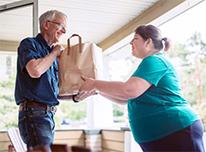 woman handing bag of groceries to senior man