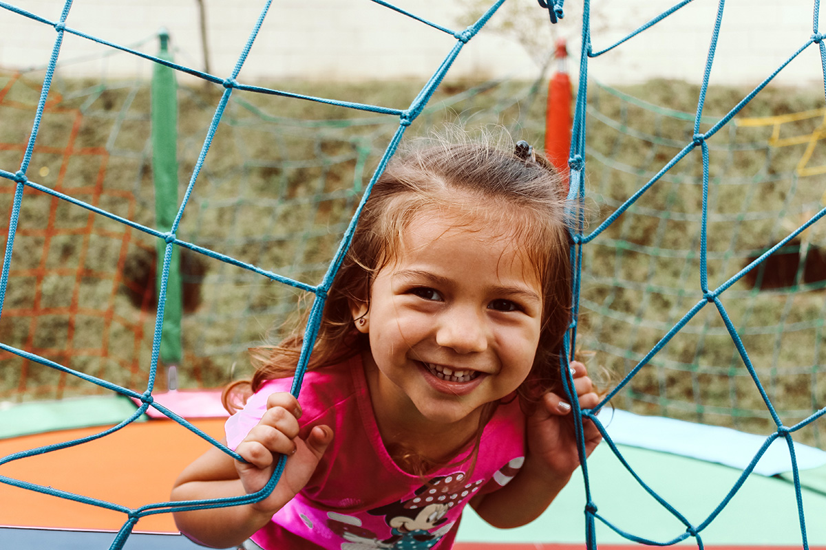 smiling child peering through net on a trampoline