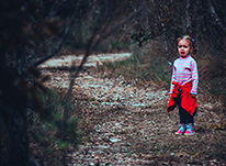 child with red sweater in woods crying