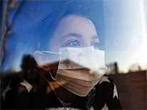 child in a mask looking out a window