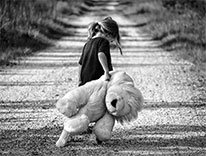 child hauling a big teddy bear