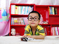 Child in glasses in front of a red bookcase