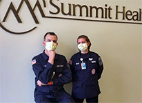 Two uch workers wearing masks under hospital sign