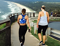 Women in workout gear walking near ocean, seen from back
