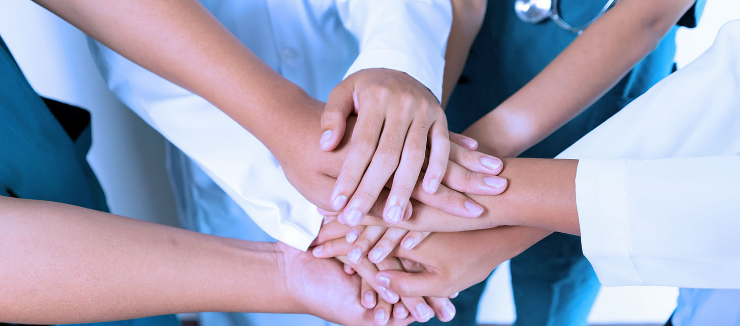 health care workers pile hands