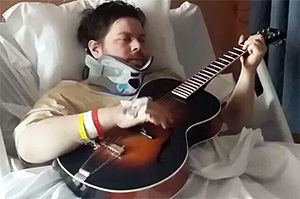 Patient playing guitar in hospital bed