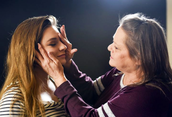 A woman rubbing another woman's faces