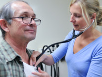 woman using stethoscope on older male patient