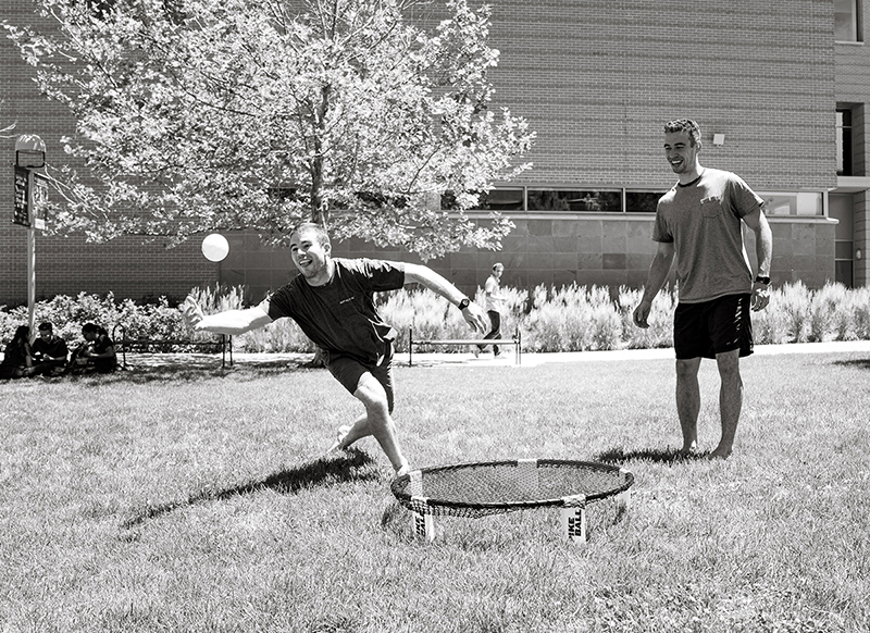 Students playing spikeball black and white