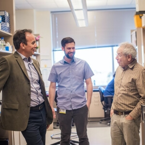 Dr. Espinosa speaks with other scientists in the lab