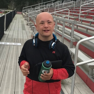 A man who has Down syndrome and alopecia aerate stands in front of bleachers and appears to be wearing workout gear, including a water bottle and headphones