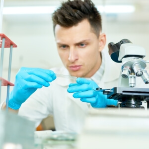Man looking at microscope slide